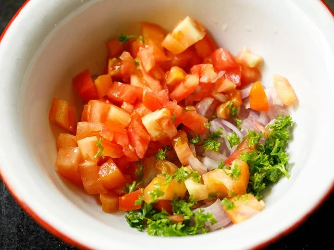 chopped onions, tomatoes and parsley in a mixing bowl