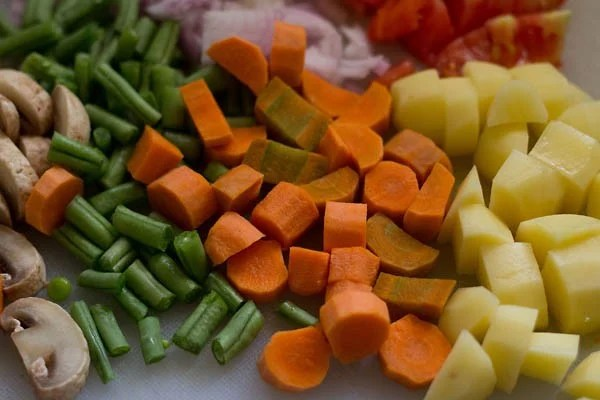 chopped carrots, green beans, potatoes, onions, tomatoes and button mushrooms on a chopping board