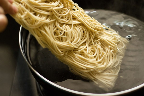 adding noodles to make schezwan noodles recipe