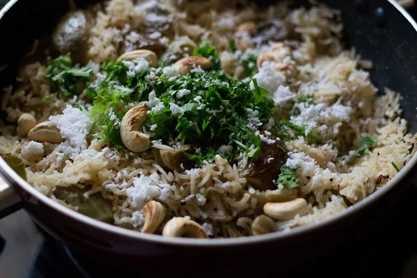 garnishing with coriander leaves and coconut