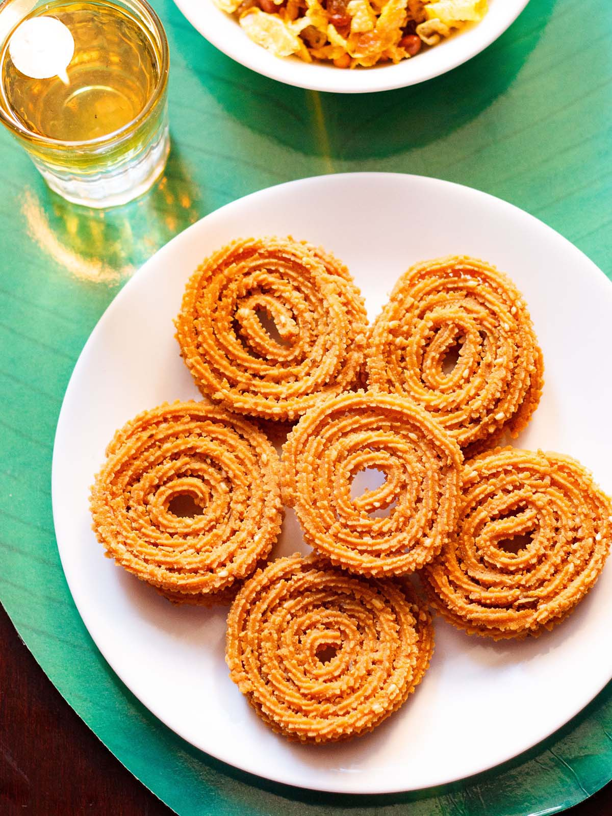 fchakli kept in a round circle with a chakli in the center on a white plate on a green background