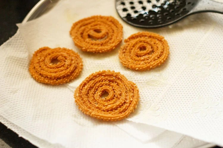 four fried chakli kept on kitchen paper towels