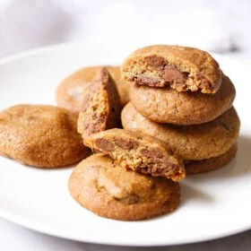 eggless chocolate chip cookies stacked and kept randomly on a white plate