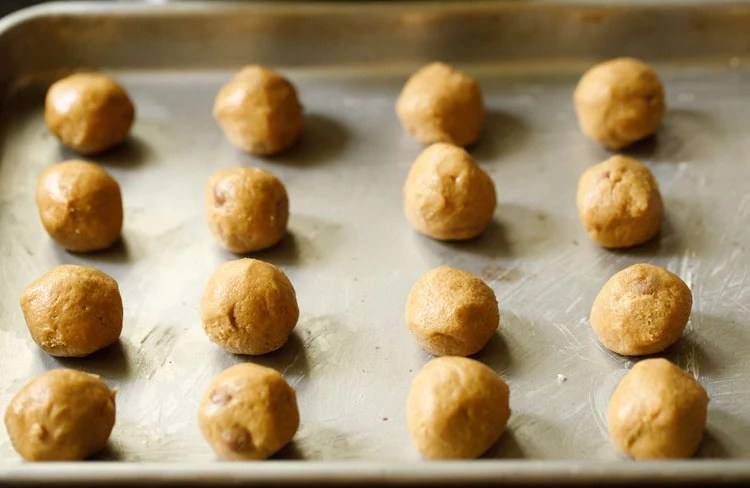 cookie dough balls placed on a greased baking tray