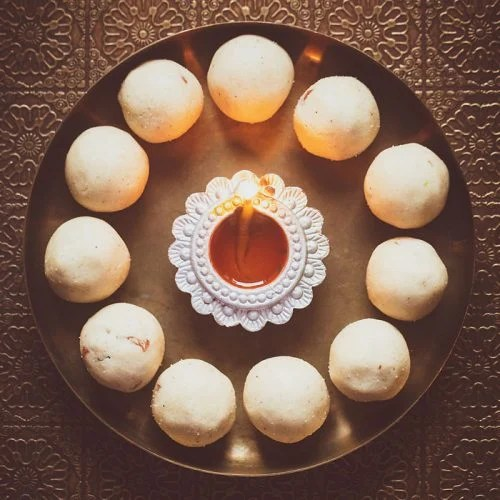 rava ladoo in a circle with lit earthern lamp in center on a bronze plate
