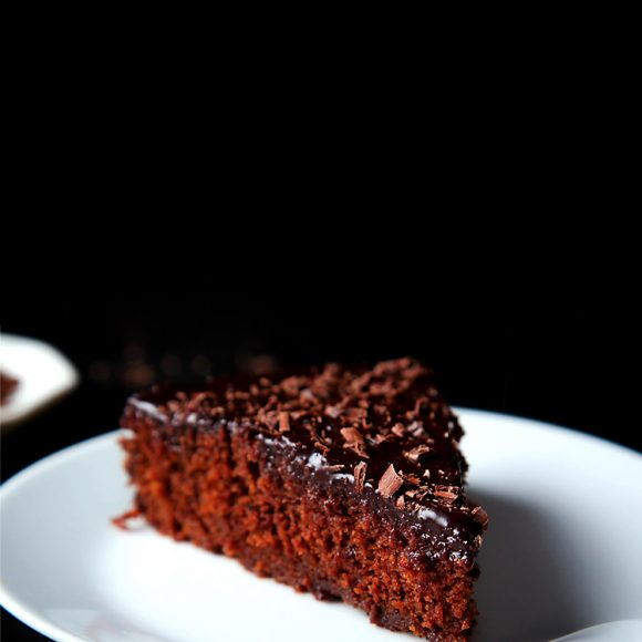 A triangular slice of eggless chocolate cake on a white plate