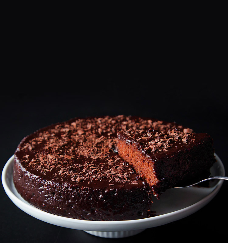 a slice of eggless chocolate cake being lifted with a spatula. The entire cake is kept on a white cake stand on a black board