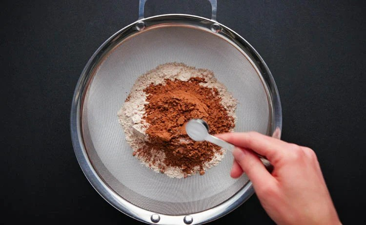 baking soda being added in the sieve