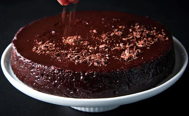 vegan chocolate cake being decorated with cacao shavings