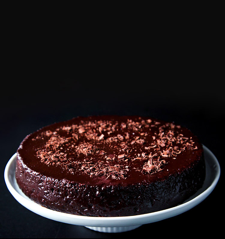 vegan chocolate cake on a white cake stand on a black board