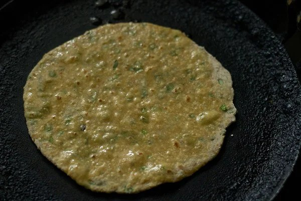 apply oil on mix veg paratha on a tawa