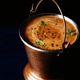 dal makhani served in a copper bucket and garnished with three cilantro sprigs