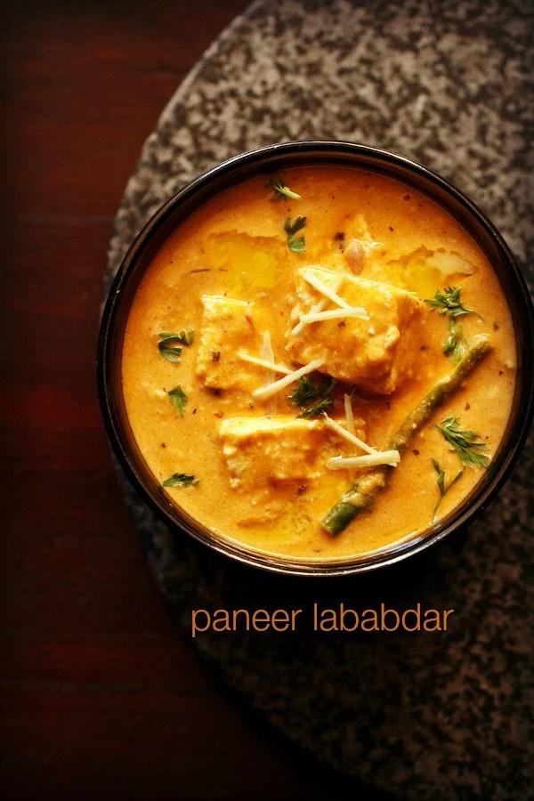 paneer lababdar in a black bowl with ginger julienne on top