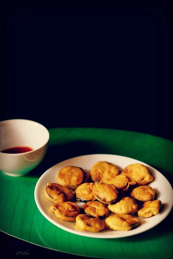 baingan pakora served on a plate with chutney in a bowl
