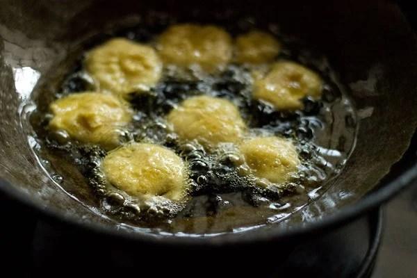 frying brinjal bajji in hot oil in a kadai