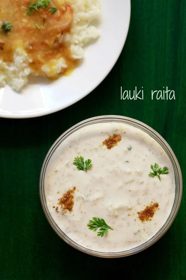 lauki ka raita in a glass bowl sprinkled with roasted cumin powder and coriander leaves on a dark green board