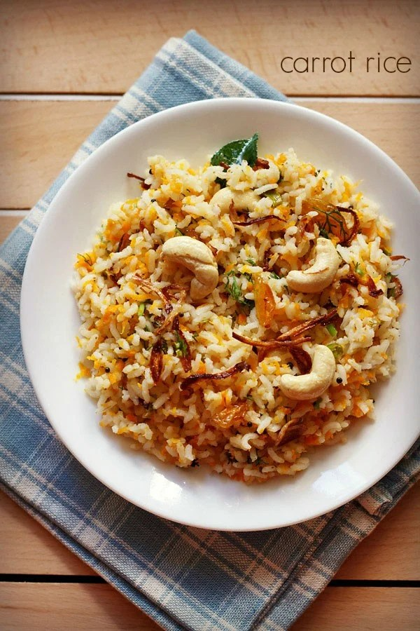 carrot rice garnished with cashews, fried onions and raisins served in a white plate on a checkered white and blue napkin