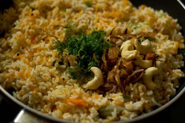 added coriander leaves and onions, cashews, raisins mixture to carrot rice