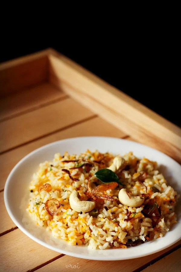carrot rice garnished with cashews, fried onions and raisins served in a white plate on a light wooden tray