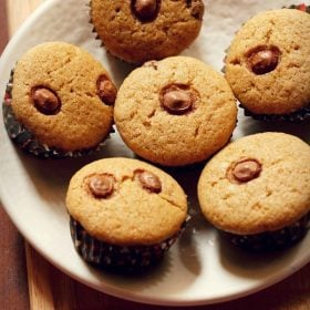eggless chocolate chip muffins arranged neatly on a round plate placed on a bamboo board