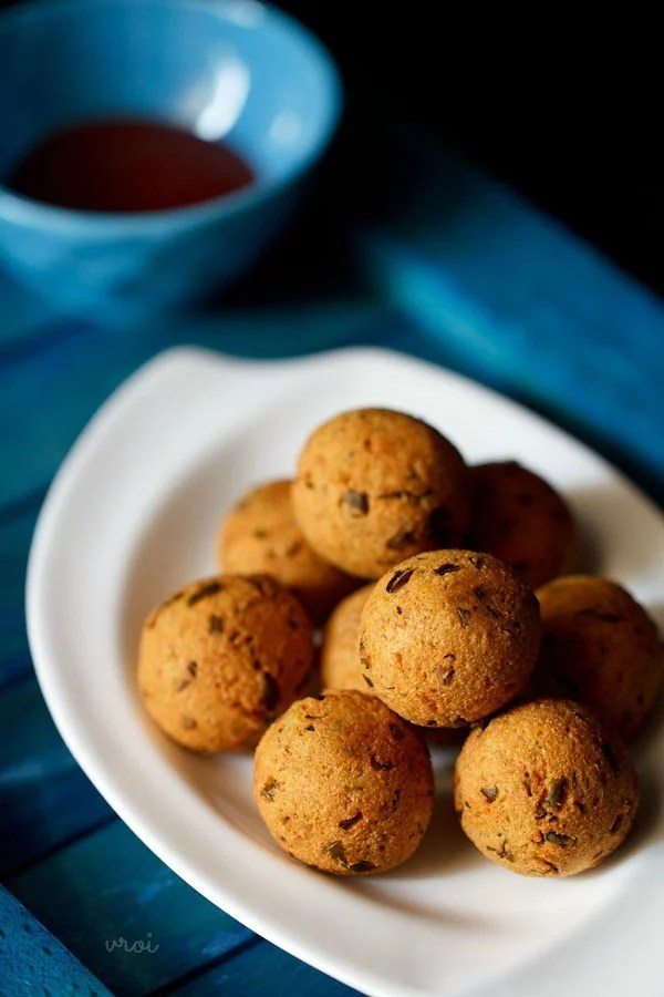 pile of Indian fried potato and cheese balls on a white serving plate on a blue cloth