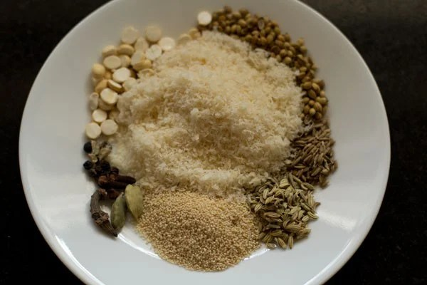 spices, nuts and seeds on a white plate to make kurma paste