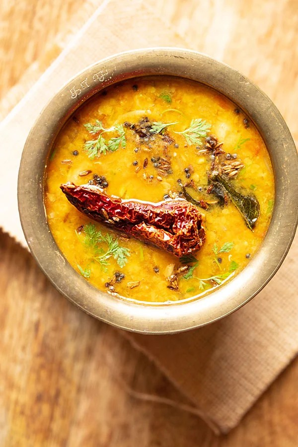 instant pot dal tadka served in a brass pot on a jute fabric on a brown wooden table
