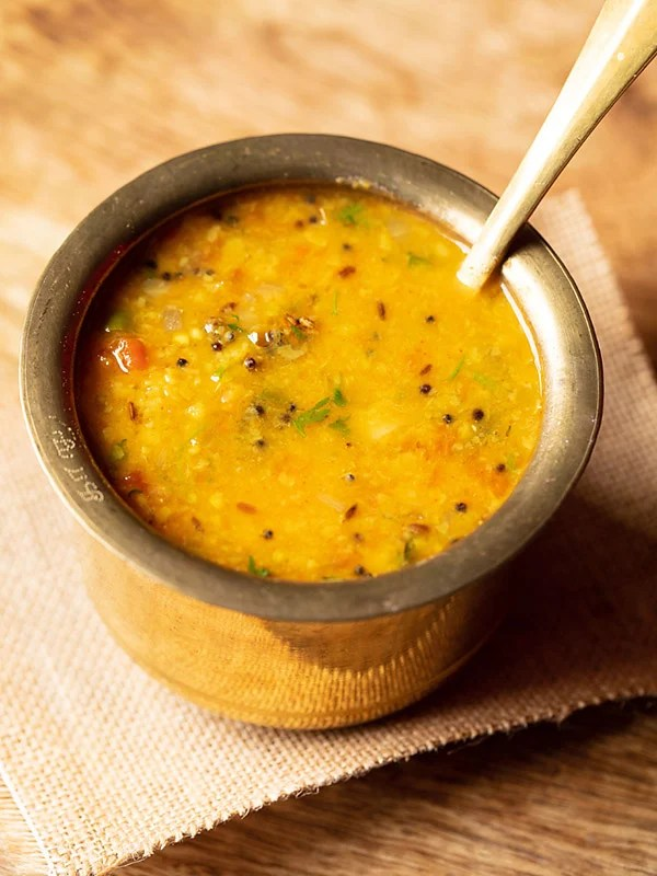 instant pot dal tadka served in a brass pot with a brass spoon inside the brass pot