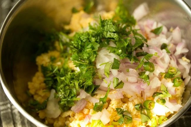 onions, spices and herbs added to the chana dal mixture in a steel mixing bowl