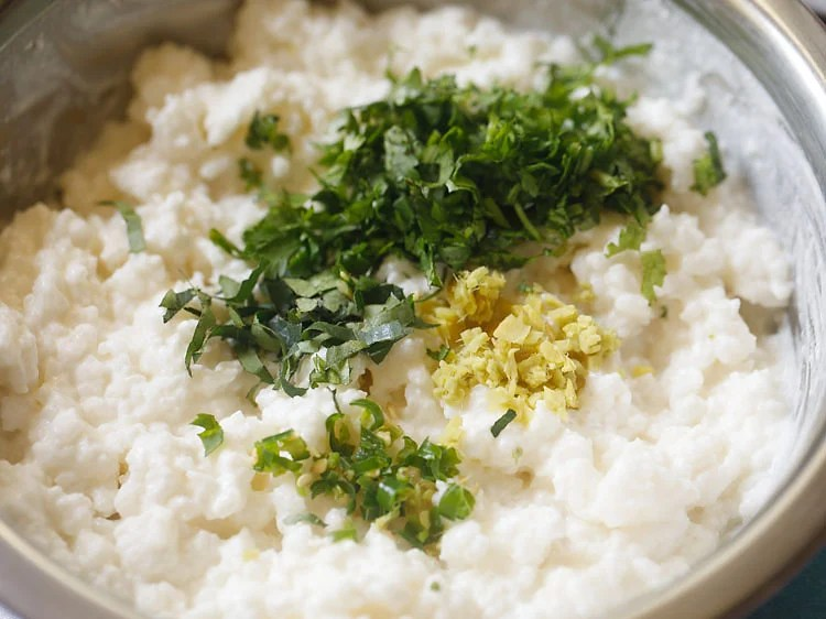 adding chopped coriander leaves, chopped green chillies, chopped curry leaves and chopped ginger in the curd rice mixture