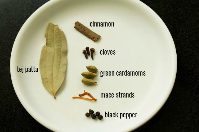 whole spices on a white plate with their names listed next to each