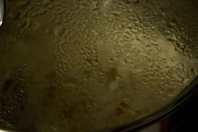 rice being simmered inside the pan covered with lid moistened with water droplets