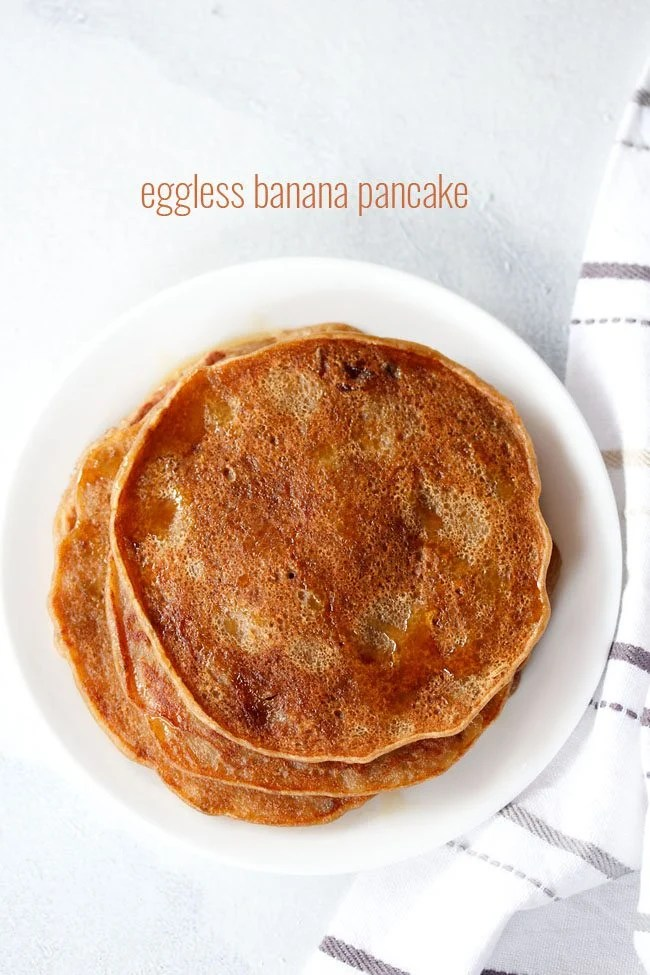 eggless banana pancakes drizzled with maple syrup on a white plate on a white board