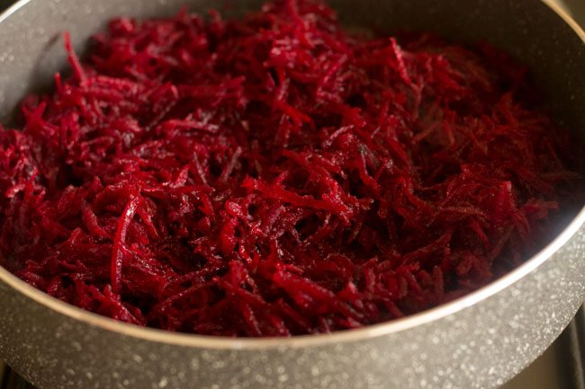 checking beetroot halwa and stirring at times