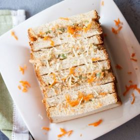 mayonnaise sandwich topped with grated carrots and cheese on a square white plate