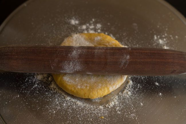 dough being rolled with a wooden rolling pin