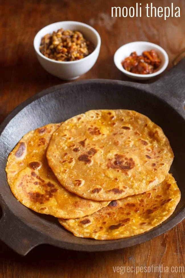 mooli thepla placed in an black round stone tray with a side of mango pickle in a small white bowl, dry chutney in another white bowl on a brown wooden board