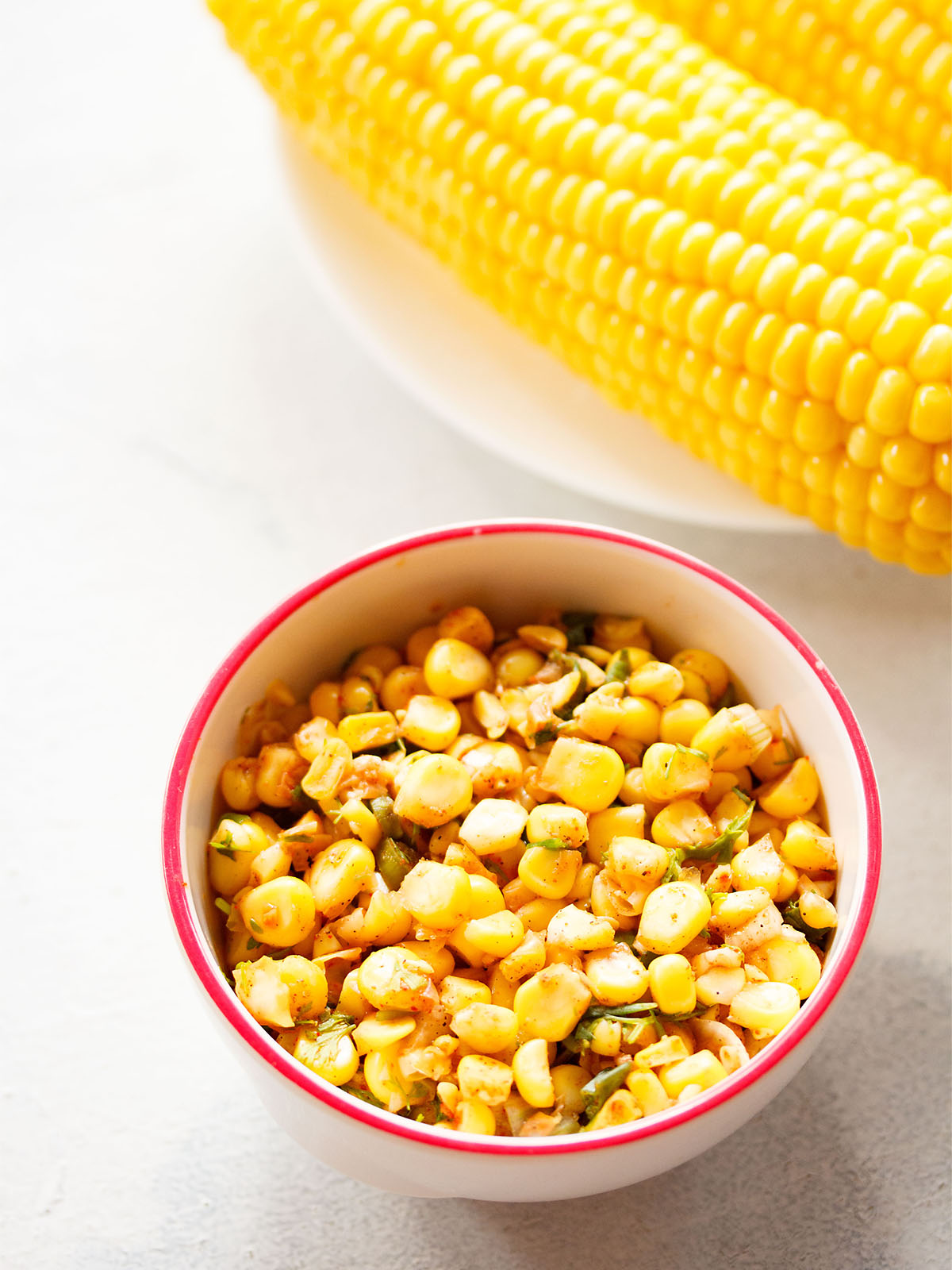 corn salsa served in a dark pink rimmed white bowl on a white background with a steamed corn cob at the side