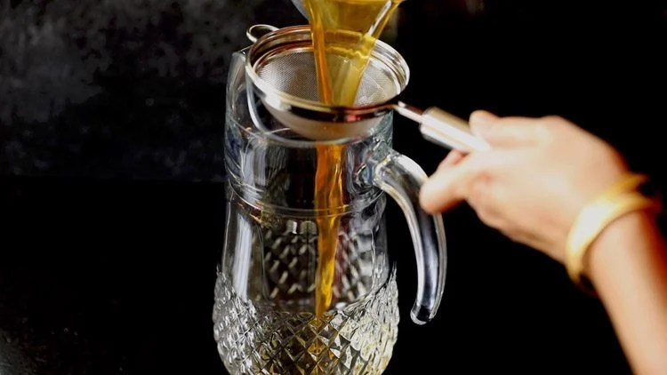 straining lemon iced tea