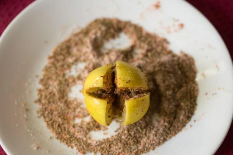 spice and salt mixture stuffed inside an almost cut lemon