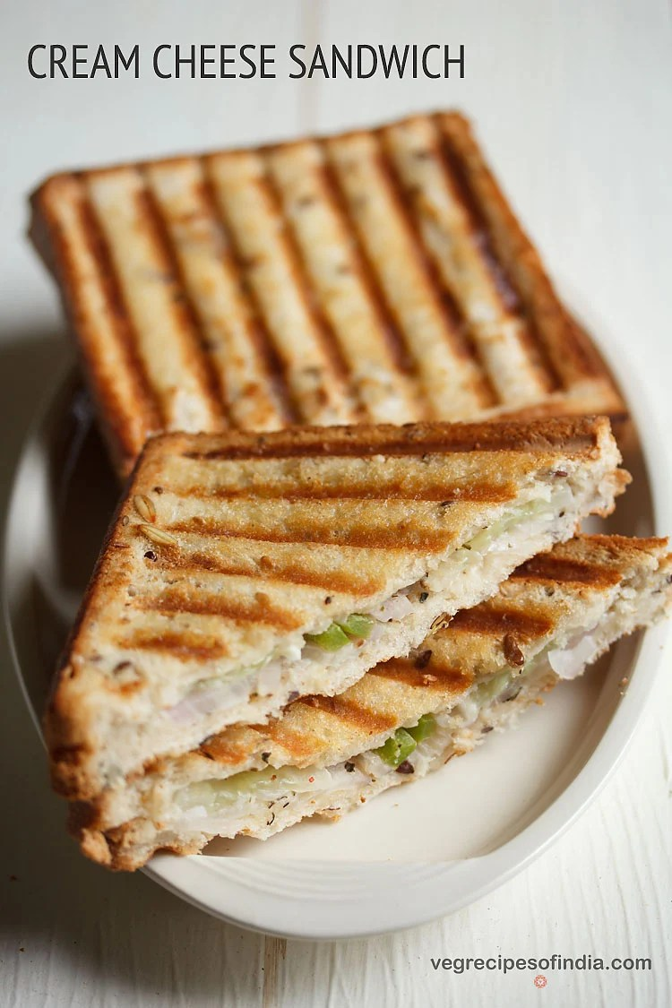 angled overhead photo of cream cheese grilled cheese sandwiches on a white plate