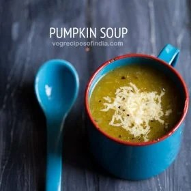 pumpkin soup topped with cheese and served in a blue soup mug with a blue spoon on a dark blue wooden board