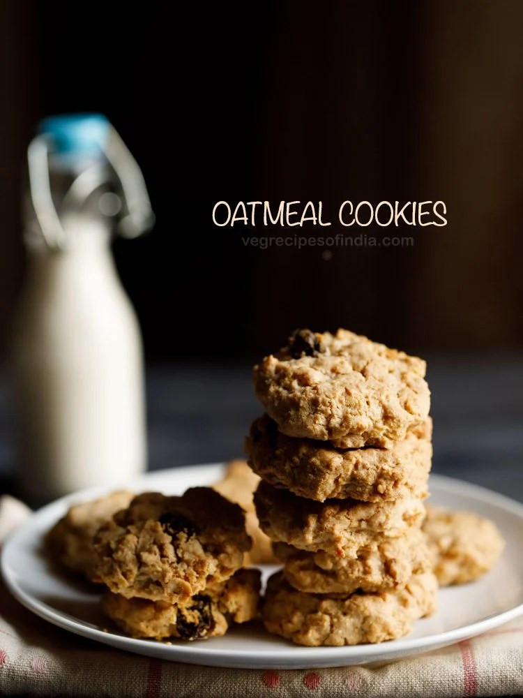 single oatmeal cookies kept on a white plate on a cream napkin with a small glass bottle of milk in the background