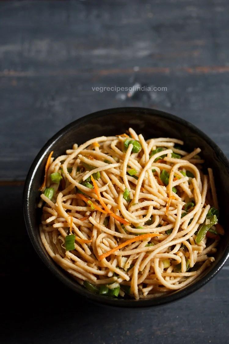 veg noodles served in a black bowl on a dark blue-gray wooden board