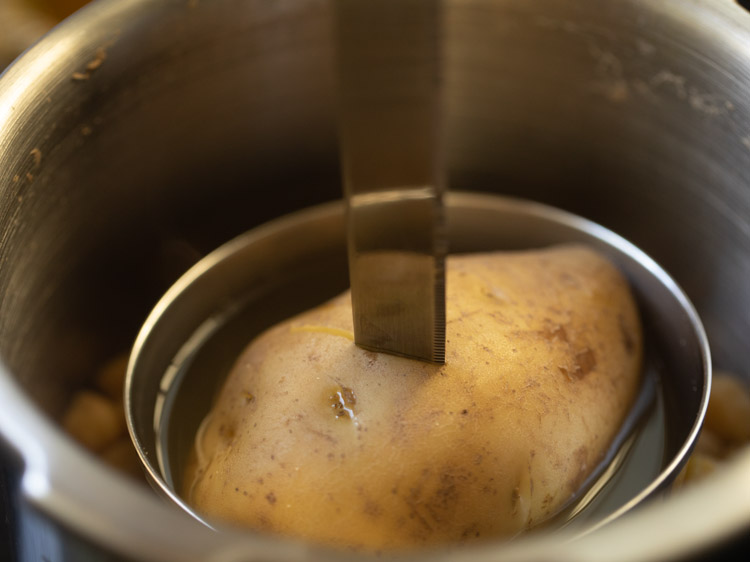 sliding a fork or knife in the cooked potato to check if it is cooked or not
