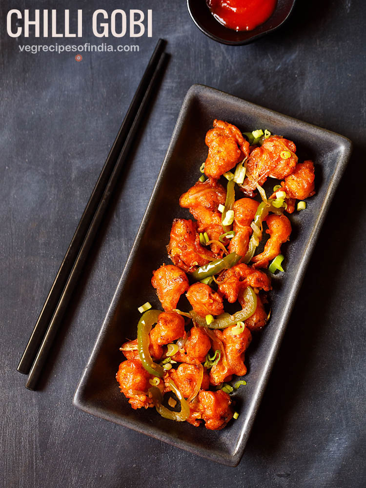 chilli gobi served in a black rectangular tray with black chopsticks on the left side on a blacking grey board