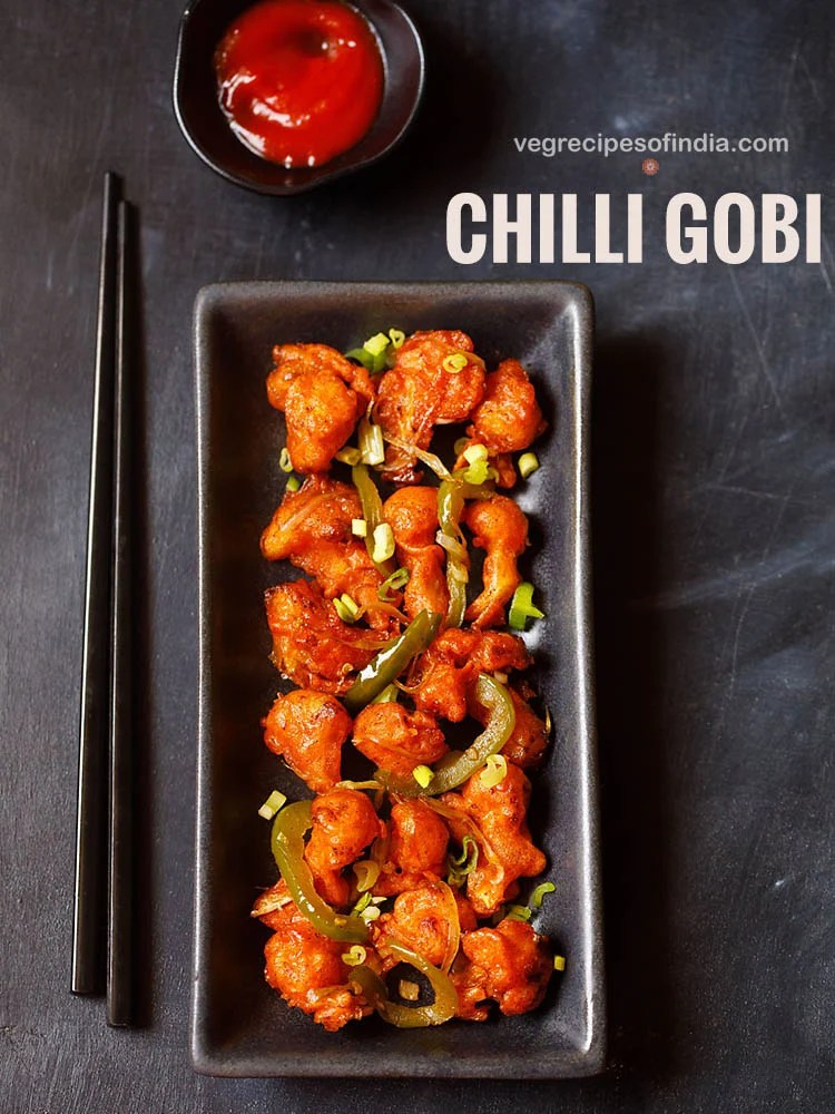 chilli gobi served in a black rectangular tray with black chopsticks on the left side on a blacking grey board with sweet red chilli sauce in a small black bowl placed on top.