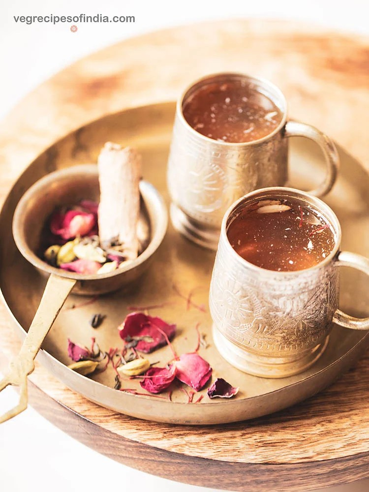 Kashmiri kahwa tea served in 2 small silver cups. a brass strainer filled with green tea leaves, spices, rose petals, saffron kept as the side.