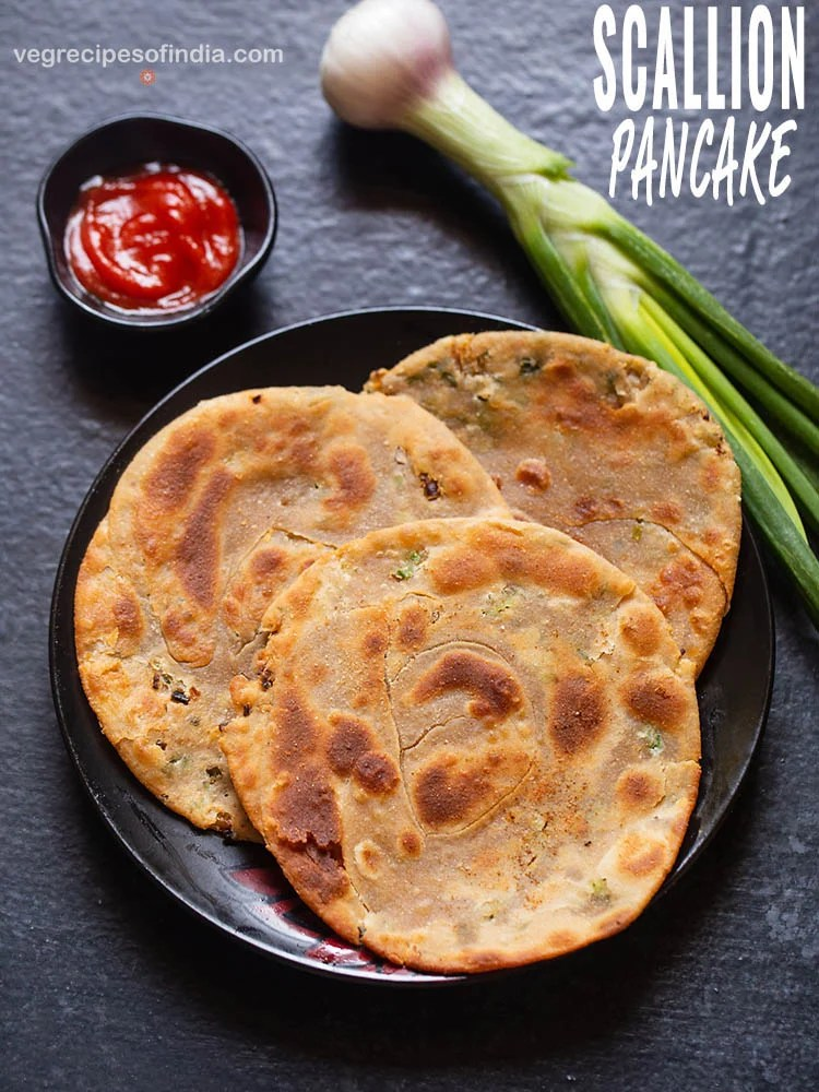 scallion pancakes placed on a black ceramic plate on a black board with sriracha sauce served in a small black bowl on left side and a stalk of spring onion placed on the right side of the plate.