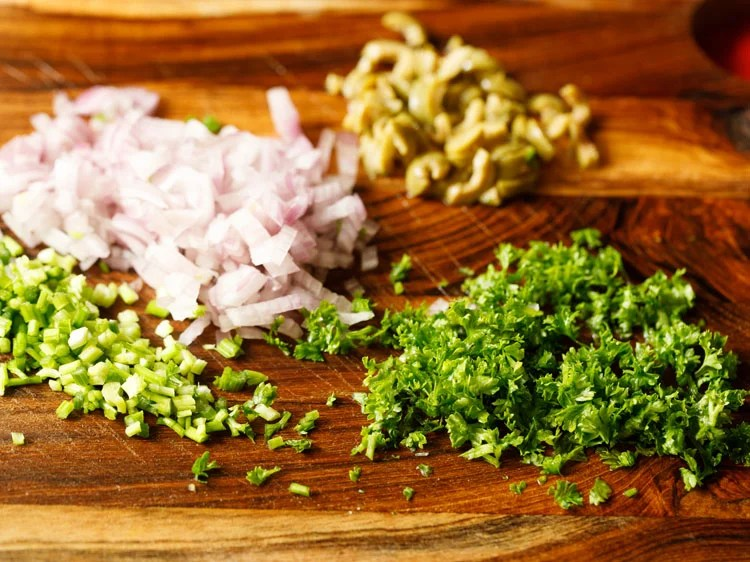 onions, celery, olives, parsley chopped on a wooden board